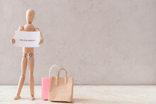 Wooden Mannequin With Text BLACK FRIDAY And Shopping Bags On Light Background