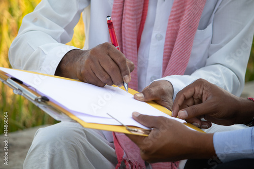 Fotografija Selective focus on farmer hands, Close up of farmer hands signing on documents while sitting near the farmland - concept of cotract farming, business deal and farm loan approval