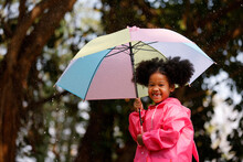 Little Curly Hair Girl Wearing Raincoat Colour Pink Good Humour As She Holds A Umbrella And She Is Fascinated By The Large Raindrops That Pelt The Umbrella.