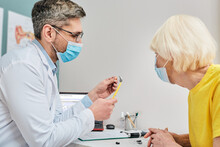 Ent Doctor Wearing A Medical Mask Shows A Hearing Aid To A Senior Woman For Treatment Of Deafness While Coronavirus Epidemic