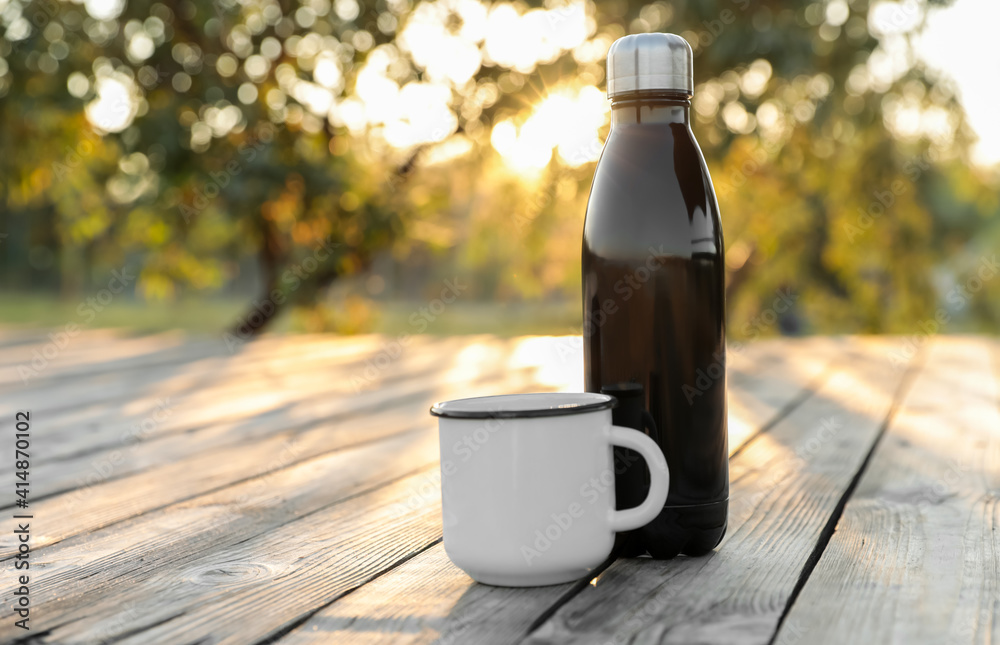 Fototapeta Modern black thermos bottle and cup on wooden surface outdoors. Space for text