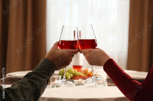 Fototapeta Couple clinking glasses of red wine on romantic dinner at home, closeup obraz
