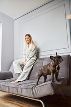 Woman Sitting On Sofa Backrest With Watchful Dog