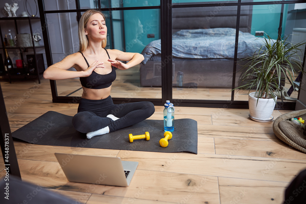 Fototapeta Woman taking a deep breath while practicing yoga