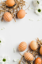 Frame Of Easter Eggs In Nests And Spring Flowers On White Background. Happy Easter Vertical Banner Mockup. Flat Lay, Top View, Copy Space.