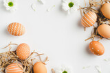 Happy Easter concept. Frame of elegant Easter eggs and spring flowers on white background. Flat lay, top view, copy space.