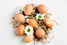 Nest With Easter Eggs And Spring Flowers On White Background. Happy Easter Concept. Flat Lay, Top View.
