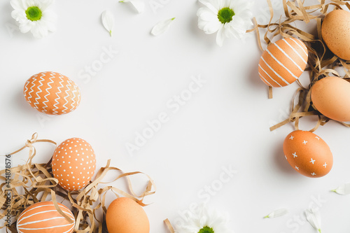 Fototapeta Happy Easter concept. Frame of elegant Easter eggs and spring flowers on white background. Flat lay, top view, copy space. obraz