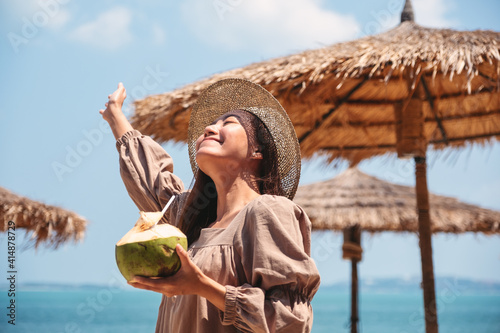 Obraz Portrait image of a beautiful asian woman holding a fresh coconut and enjoying on the beach - fototapety do salonu