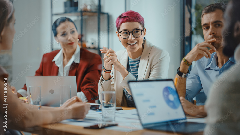 Fototapeta Office Meeting in Conference Room: Beautiful Specialist with Short Pink Hair Talks about Firm Strategy with Diverse Team of Professional Businesspeople. Creative Start-up Team Discusses Big Project