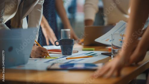 Diverse Multi-Ethnic Team of Professional Businesspeople Meeting in the Modern Office Conference Room. Creative Team Gathers Around Table to Discuss Plan Strategy. Close-up Shot with Focus on Hands