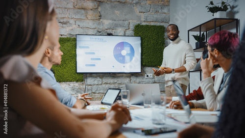 Office Conference Room Meeting: Black Chief Company Strategist Doing TV Presentation to a Diverse Team of Multi-Ethnic Professional Businesspeople, Explaining Marketing Strategy, Data Analysis - fototapety na wymiar