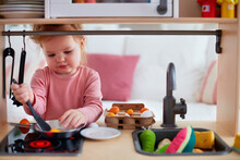 Cute Toddler Baby Girl Playing On Toy Kitchen At Home, Pretends Frying Eggs