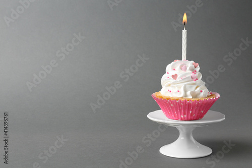 Fototapeta Delicious cupcake with candle on grey background. Space for text obraz