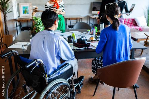 Obraz 車椅子に乗った若い社員が活躍する、多様性のある会社 - fototapety do salonu