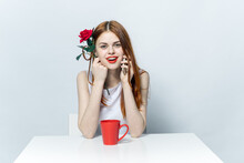 Pretty Woman Sitting At The Table With Red Rose Flower And Talking On The Phone
