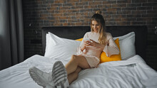 Happy Woman Smiling While Messaging On Smartphone In Bedroom