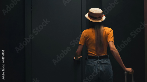 Fotografie, Tablou back view of tourist in straw hat standing with luggage near door in hotel room
