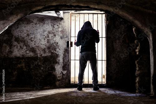 Fotografering Prisoner man locked up standing in old underground cellar , silhouette from behi