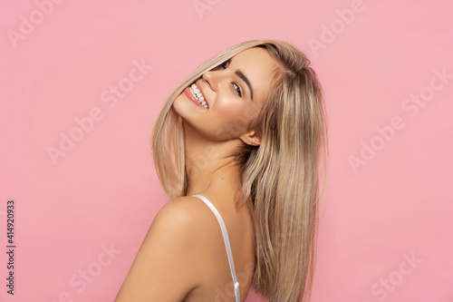 Fototapeta Portrait of happy blonde woman with long straight hair isolated on pastel backgr