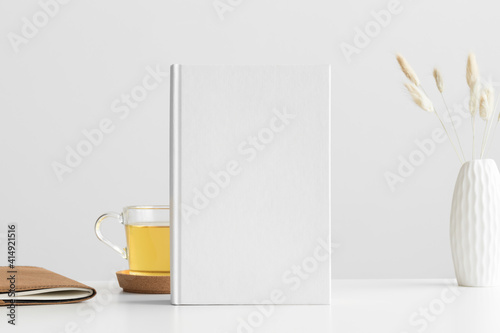 Fototapeta White book mockup with a lagurus and workspace accessories on a white table. obraz