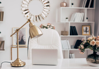 female office with a workspace desk in a light modern style with white furniture with laptop on table