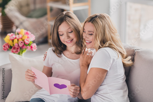 Fototapeta Photo of shiny cute daughter mom wear white t-shirts smiling looking presenting gift card sitting sofa indoors inside room home obraz