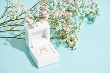 Romantic Surprise For Her. White Gift Box With Engagement Diamond Ring And Beautiful Fresh Spring Flowers On Blue Background