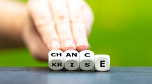 """Hand Turns Dice And Changes The German Word """"Krise"""" (crisis) To """"Chance"""" (chance)."""