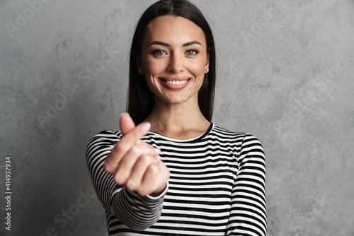 Leinwand Poster Smiling young woman snapping fingers looking at camera