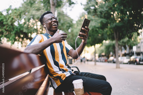 Joyful hipster guy in glasses for vision correction laughing while watching funny video vlog using cellular for online phoning, cheerful male blogger in headphones listening received audio message - fototapety na wymiar