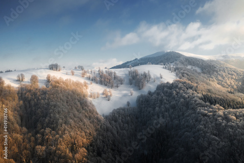 Amazing aerial view of mountains range, meadows and snow-capped peaks in winter time. Forest with frost glowing with bright warm sunrise light