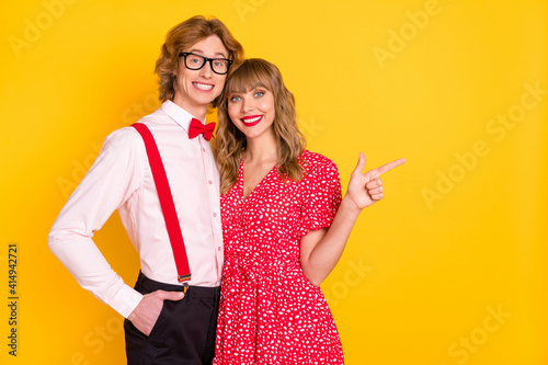 Fototapeta Photo portrait of lovely couple girl pointing finger on blank space promoting isolated on vibrant yellow background obraz