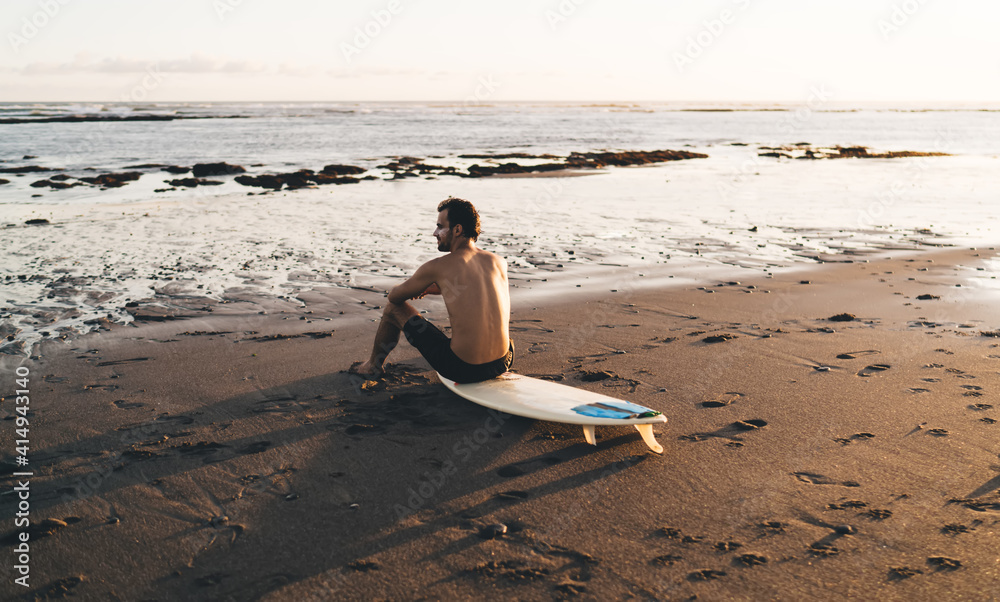 Fototapeta Male surfer relaxing on beach and looking at sea waves