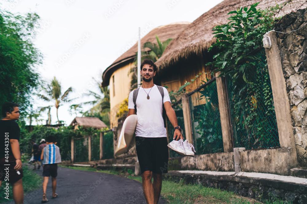 Fototapeta Cheerful surfer walking on road with surfboard in summer
