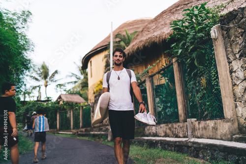 Fototapeta Cheerful surfer walking on road with surfboard in summer obraz