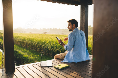 Young male tourist working remotely with smartphone and netbook in meadow during summer holidays