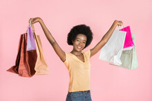 Shopping, Sales, Black Friday Concept. Cute Pleasant Dark Skinned Girl With Perfect Smile And Afro Hair, Standing With Pile Of Shopping Bags In Both Hands Raising Up, Isolated Over Pink Background
