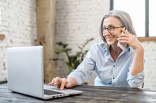 Senior Bossy Businesswoman Has Phone Conversation Working With A Laptop At The Desk In Office. An Aged Saleswoman Talking With A Customers By Smartphone. Smiling Old Woman Speaking On The Smartphone