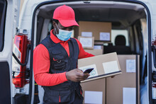 African Delivery Man With Package And Smartphone Wearing Surgical Face Mask For Coronavirus Outbreak