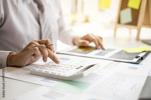 Canvas Print A business man is using a calculator to calculate company financial figures from earnings papers, a businessman sitting in his office where the company financial chart is placed