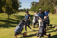 Four Caucasian Senior Men And Women Walking Across Golf Course Holding Golf Bags