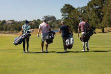 Four Caucasian Senior Men And Women Wearing Face Masks Walking Across Golf Course Holding Golf Bags