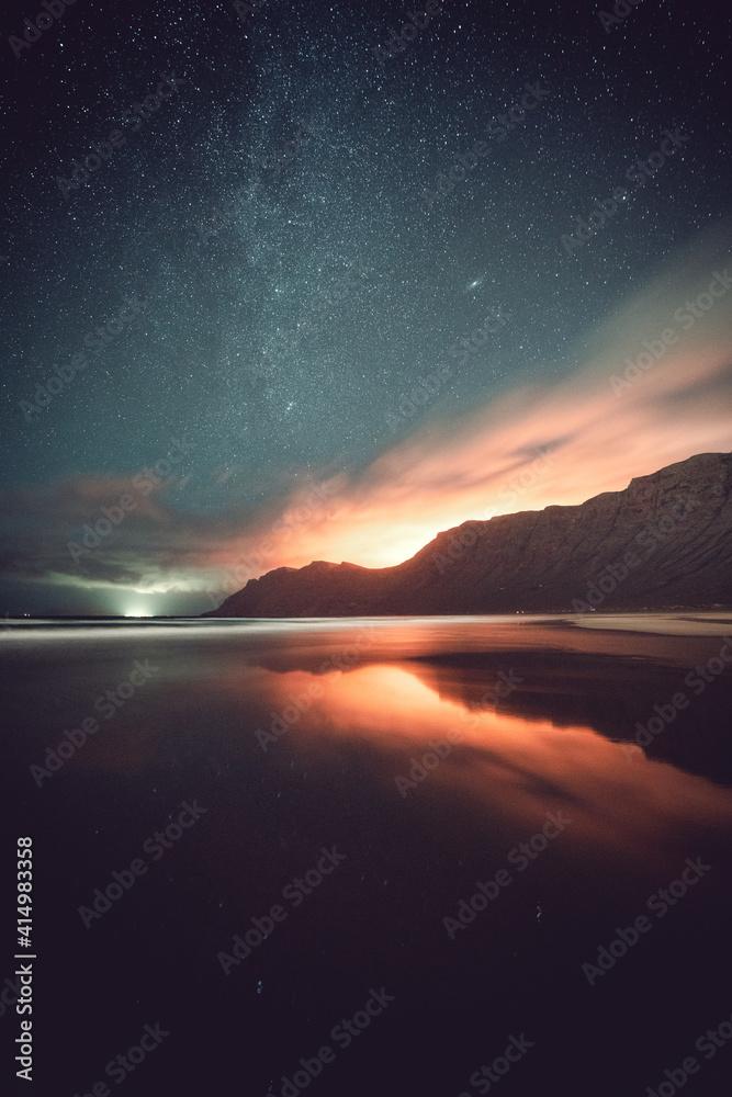 Fototapeta Vertical shot of a starry sky over a tranquil sea