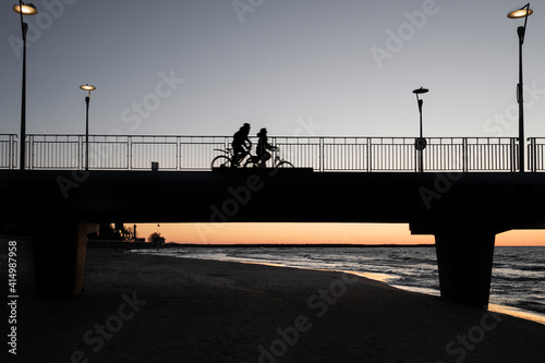 Fototapeta Sylwetka pary rowerzystów na molo w Kołobrzegu o zachodzie słońca obraz