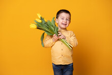 Smiling Little Boy On Yellow Studio Background. Cheerful Happy Child With Tulips Flower Bouquet