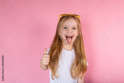 Fotografia Little girl in sunglasses showing tongue showing cool on pink background