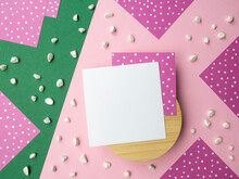 Abstract Flatlay Square Note Sheets On Round Wooden Base,pink Green Diagonal Paper Background,corners Of Lilac Paper With White Polka Dots Around Perimeter,scattered Pebbles.Design Pattern Copy Space.
