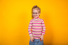 Funny Little Girl With Glasses In A Striped Jacket Standing On A Yellow Background With Markers In The Pockets Of Her Jeans