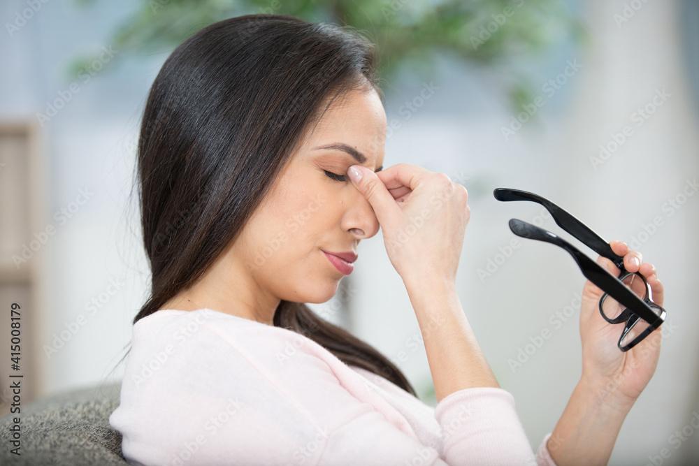 Fototapeta woman holding eyeglasses and rubbing the bridge of her nose